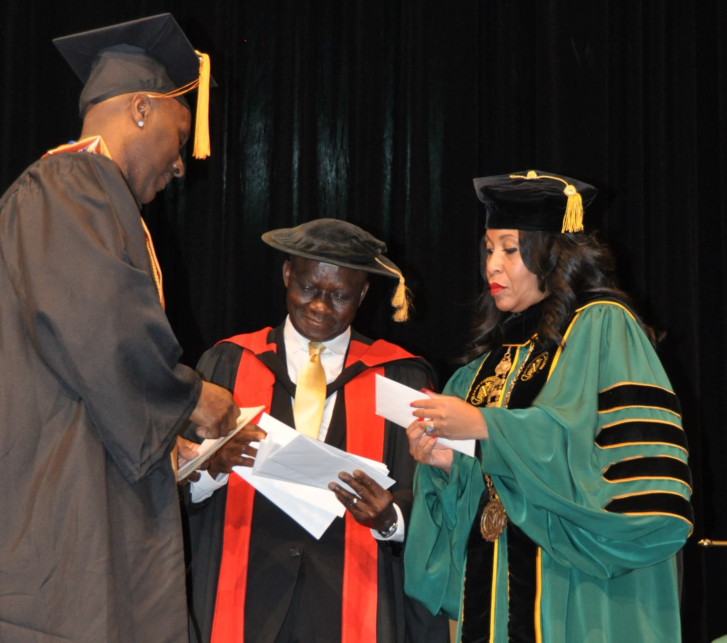 Dr. David Adegboye, vice chancellor of Academic, Evening & Weekend Affairs (center), presents a scholarship to a graduate during the Delgado Community College Commencement Exercises on Tuesday, Dec. 17, 2019. Delgado Chancellor Larissa Littleton-
